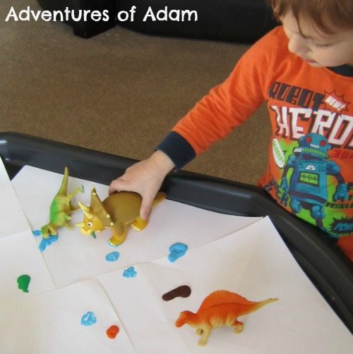Adventures of Adam Toddler painting with dinosaurs